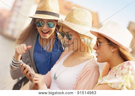 A picture of three friends using smartphone in the city