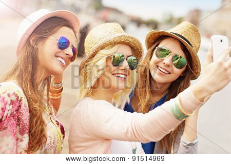 A picture of three friends taking selfie in the city