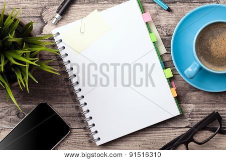 Office table with a coffee cup, a blank notepad and a plant