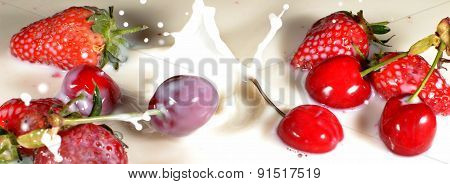 Strawberries And Cherries Dropping Into Milk