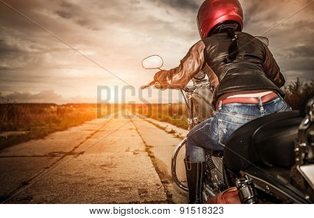 Biker girl in a leather jacket and helmet on a motorcycle. Focus on the fuel tank