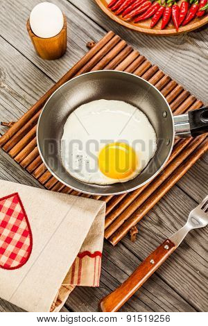 Fried eggs on a wooden table, breakfast