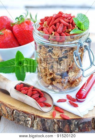 Muesli with dried goji berries and mint on a wooden backgraund