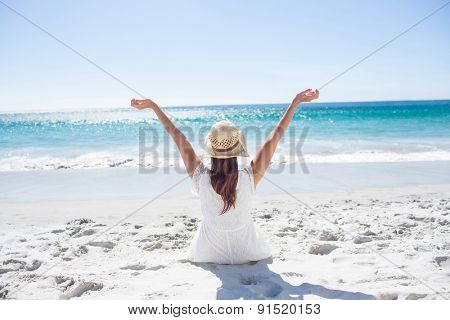Brunette sitting in the sand and enjoying the air at the beach