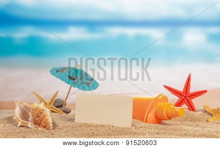 Card and cockleshells on sand