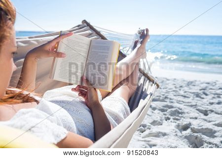 Brunette reading a book while relaxing in the hammock at the beach