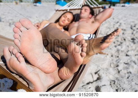 Happy couple napping together in the hammock at the beach