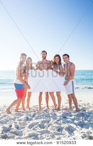 Happy friends holding poster at the beach