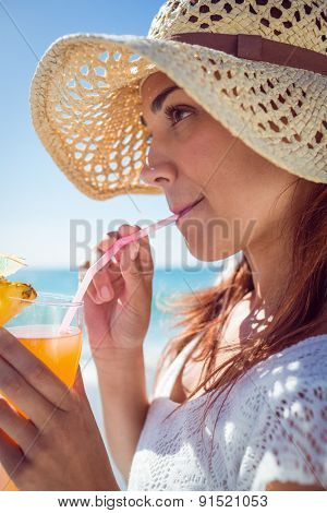 Brunette wearing straw hat and drinking a cocktail at the beach