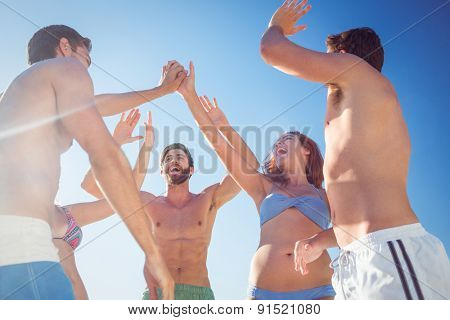 Group of friends standing in circle arms raised at the beach