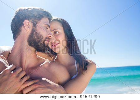 Happy couple hugging and smiling at each other at the beach