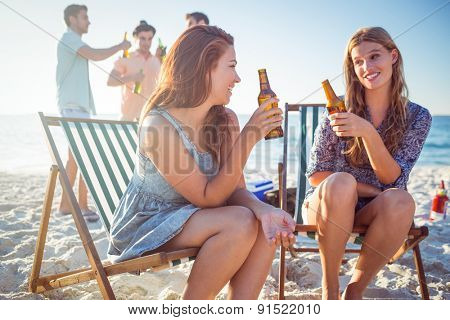 Happy friends doing barbecue and drinking beer at the beach