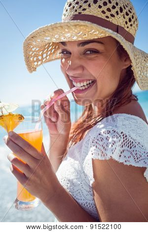 Smiling brunette wearing straw hat and drinking a cocktail at the beach