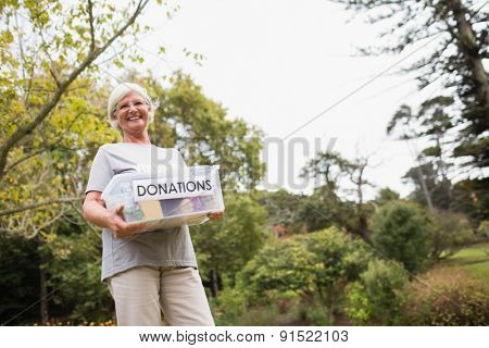 Happy grandmother holding donation box on a sunny day