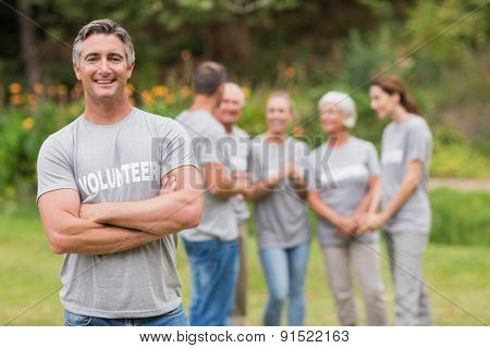 Happy volunteer looking at camera with arms crossed on a sunny day