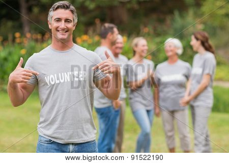 Happy volunteer showing his t-shirt to camera on a sunny day