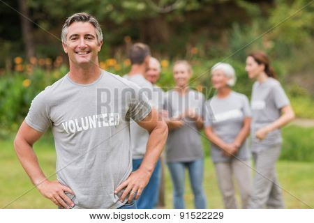 Smiling volunteer looking at camera on a sunny day