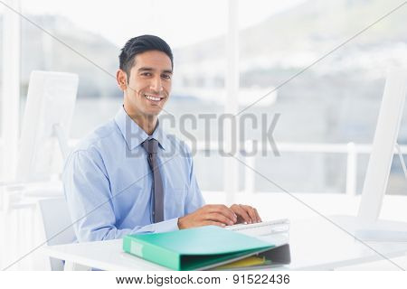 Smiling businessman using computer in office