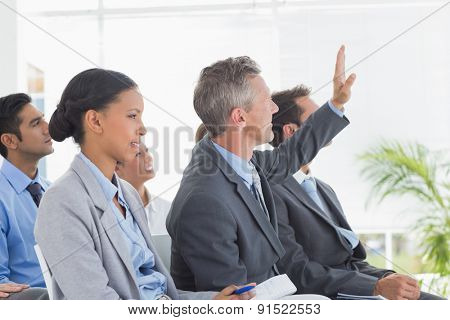 Businessman asking question during meeting in office