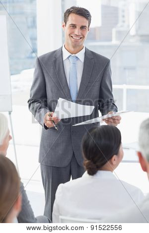 Happy businessman looking at camera during meeting in meeting room