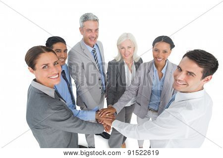 Portrait of happy executives holding hands together in the office