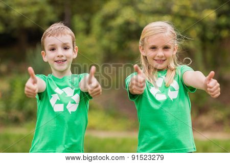 Happy siblings in green with thumbs up on a sunny day