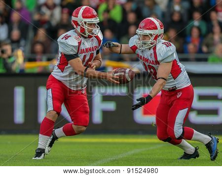 GRAZ, AUSTRIA - MAY 31, 2014: QB Kasper Skyum Jensen (#14 Denmark) hands off the ball to RB Lars Hyrsting Larsen (#18 Denmark) in match against Austria during the EFAF European Championships 2014 in Austria.