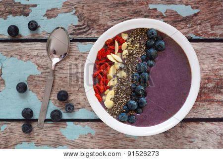 Blueberry smoothie bowl with on a rustic old wood background