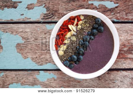 Blueberry smoothie bowl with superfoods on rustic old wood
