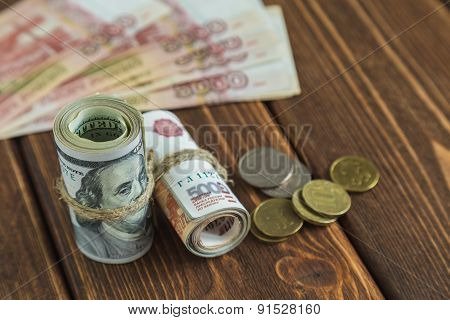 Dollars and rubles stack on the wood desk