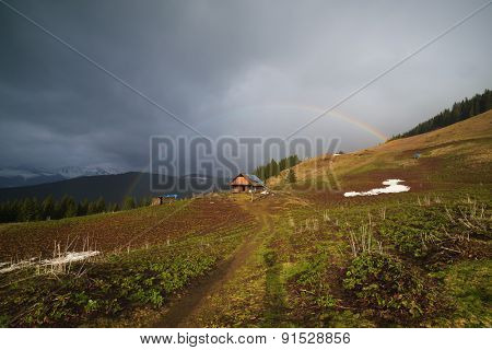 Landscape in the mountain village. Rainbow over the house