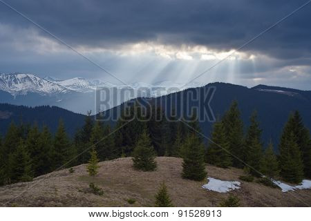Spring landscape in the mountains. Sun rays through the clouds. Beauty in nature