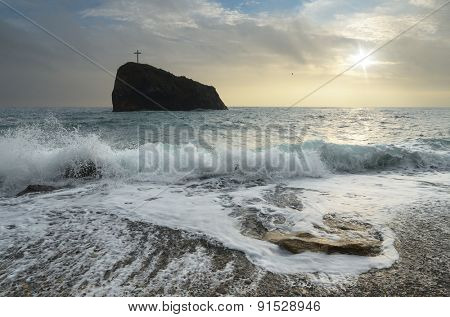 Seascape with storm. Rock with a cross in the sea. Crimea