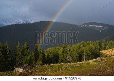 Spring landscape with a rainbow in the mountains. Beauty in nature