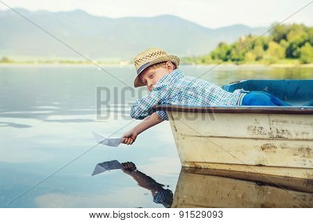 Little Boy Launch Paper Ship Lying In Old Boat