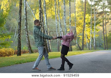 Young couple walking in a park in autumn gold