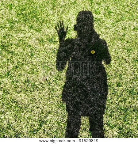 Shadow Of A Woman Waving Her Hand