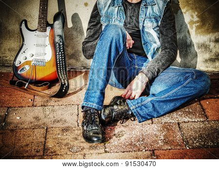 Guitar And Man Against The Wall