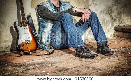 Man And Guitar Leaning Against A Wall