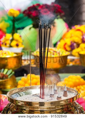 Offerings To Gods With Burning Incense Aroma Sticks , Flowers And Food .