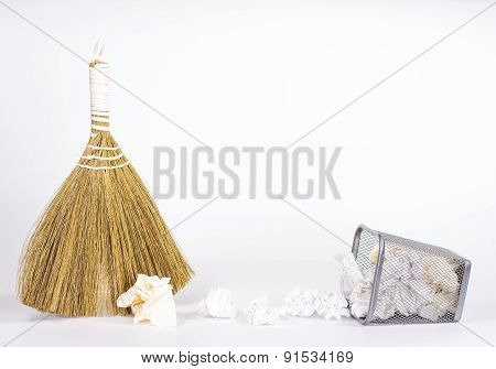 isolated besom and fallen wastebasket full of white waste paper