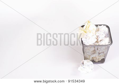 isolated wastebasket full of white waste paper and paper ball