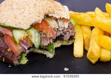 Half Eaten Cheeseburger and Fries