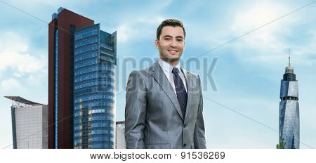 Portrait Of A Cheerful Young Businessman, Modern Business Buildings Behind. Smart Friendly Man. Outd