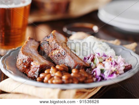 barbecued spare ribs with coleslaw, potato salad, and baked beans