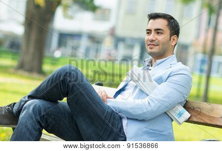Young Gorgeous Man Sitting On Bench In A Park, Outdoor - Outside