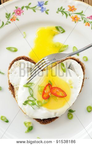 Fried Egg Heart Rye Sandwich With Scallion, Chili And Fork On White Plate