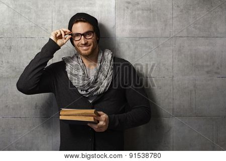 Happy, young man holding book, looking at camera, leaning against grey wall.