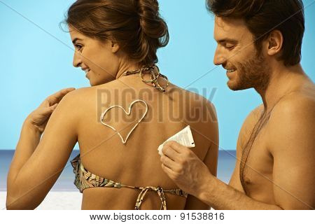 Playful happy young handsome caucasian man putting sun cream on back of woman in swimsuit before sunbathing at the beach. Smiling, having fun, creativity.