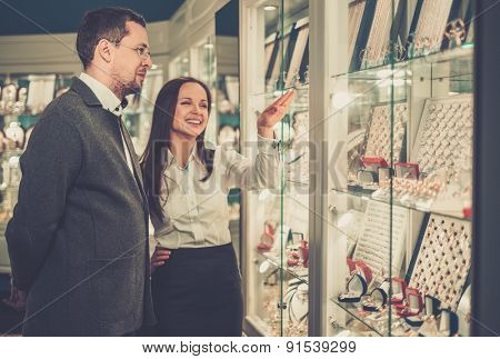 Man with assistant help choosing jewellery